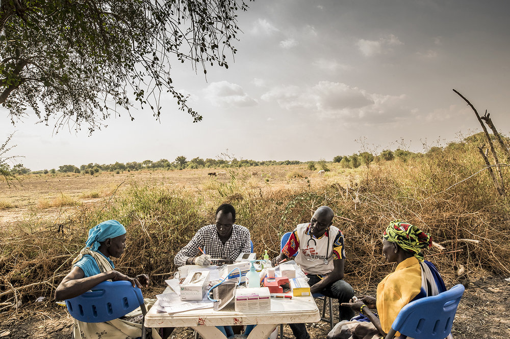 In the shade of a tree, medical workers give consultations, at a mobile clinic. Once a week, MSF Switzerland settles on trees in the village of Kier, on the banks of the Pibor River.