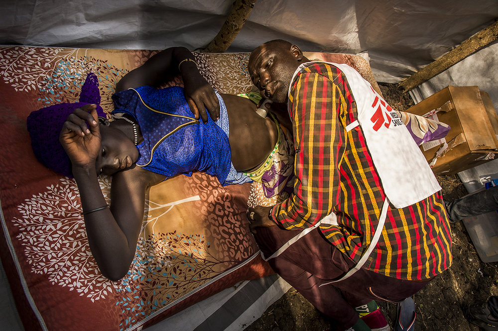 Village of Kier, along the Pibor River, border between Ethiopia and South Sudan. John Lam examines a pregnant woman lying on a mattress brought for the occasion, in a consultation area of the mobile clinic of MSF Switzerland, set up for the day.  Made up of 6 people (nurses, medical workers and drug dispenser), it received 43 patients. This site, 1.5 hours from Akobo, the last city held by the rebellion, was identified by MSF Switzerland to build a logistics base and a health center for the population, in fact opposition supporters. Indeed, the analysis of the dynamics of the current civil war suggests that government troops will attack Akobo, sooner or later as it is a strategic crossroads and the last urban center held by the rebellion. The inhabitants will certainly flee and disperse in the bush along the river towards the south or the north. MSF Switzerland expect that the people will come to one of the 7 points to seek help, including this one, the furthest from the expected Governmental military push.