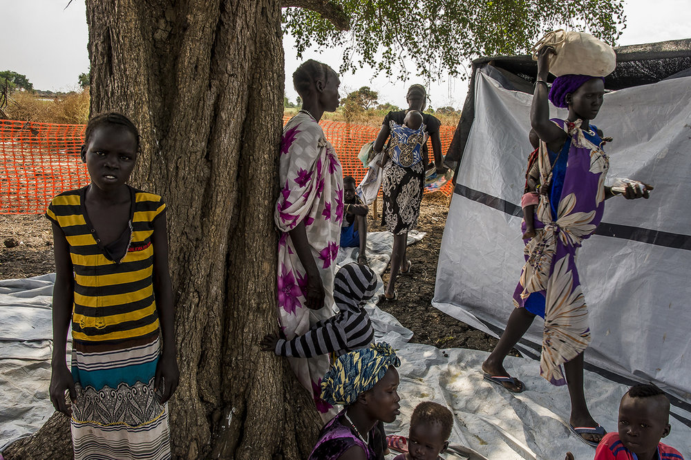 Village of Kier, along the Pibor River, border between Ethiopia and South Sudan. Patients and their children wait to be seen by a medical assistant in one of the two temporary consultation rooms of a mobile clinic set up for the day.