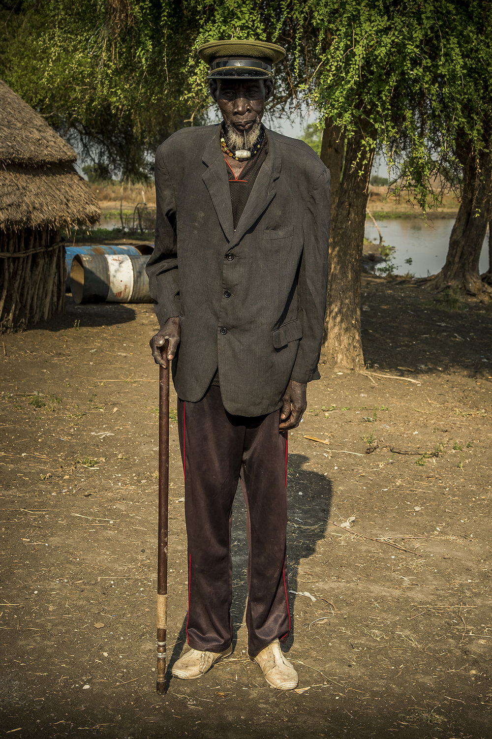 Riek Duor, more than 80 years old as far as he remembers, posing along the banks of Pibor river, somewhere in Upper Nile State, in opposition stronghold, South Sudan. A man proud of his cap which he wears since he was in the Sudan army, a long time ago, before independence in 1956.