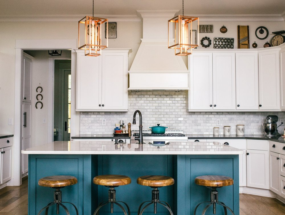 The warm copper tones of these  Geometric Long  pendants spice up this kitchen and accent the saturated blue-green tone of the central island as well as the bronze cabinetry hardware and fixtures.