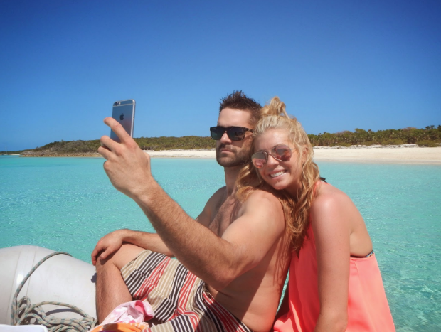 Taking a selfie, Tyler and Meg pose on our dinghy after a swimming pig feeding at Big Major Cay, Exumas, Bahamas