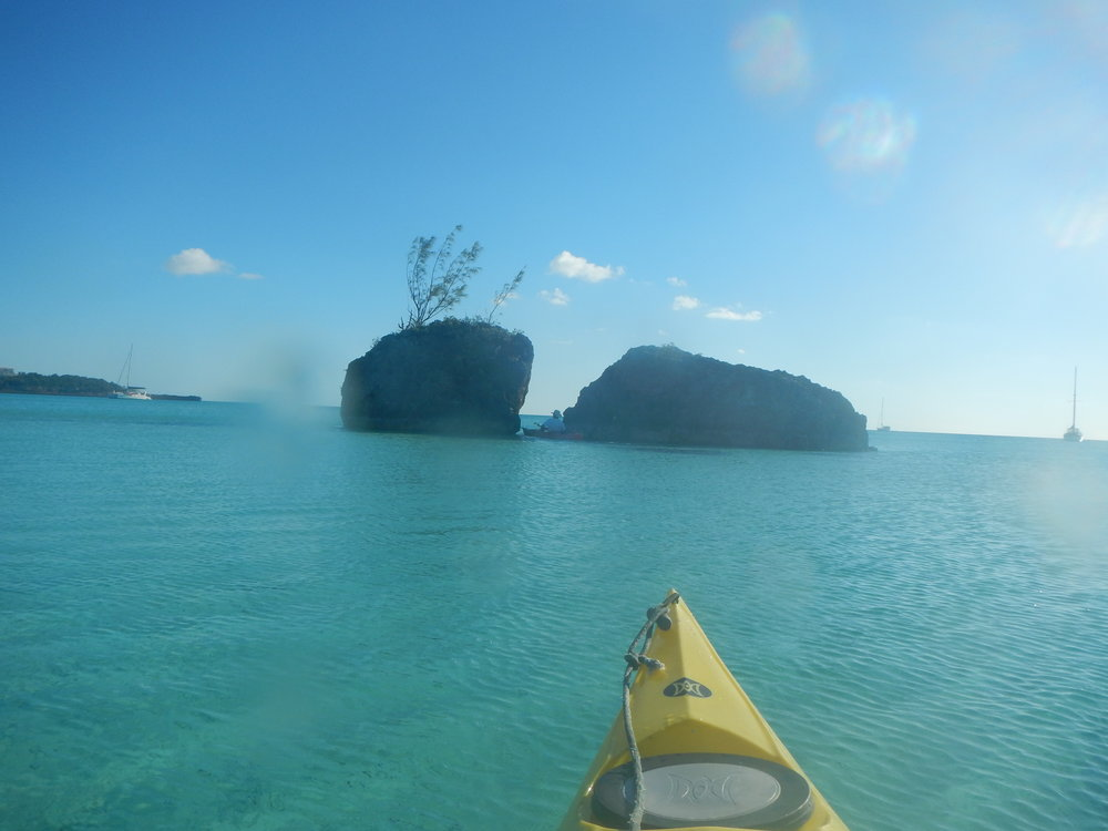 As I follow, Clint paddles through a rock and a hard place near the Glass Window, Eleuthera.