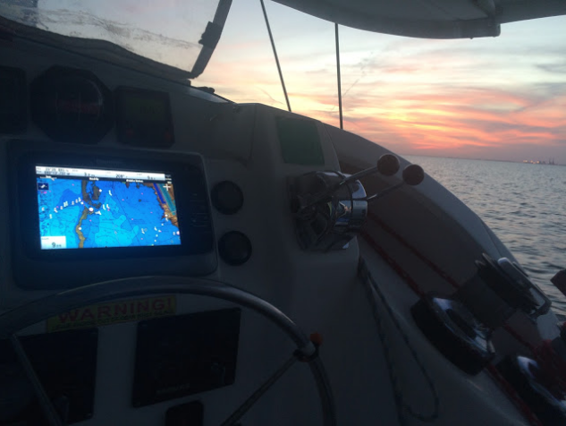 Mystique's Raymarine GPS navigator aid; a southern Florida power plant in the distance at sunset of my solo.