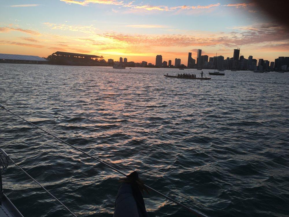 A canoe of paddlers heading towards Marine Stadium passes by  Mystique  near sunset.