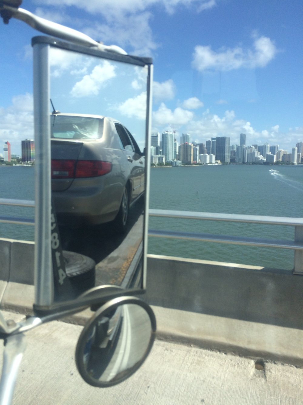 A tow truck carrying my car across the Rickenbacker bridge with Miami skyline in the distance. Does it appear my Honda is driving off the bridge? How do you know it is not?
