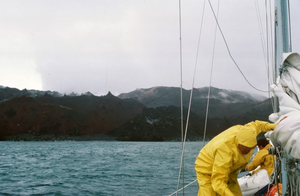 That's I kneeling on the foredeck dousing and furling the jib as  Reindeer heads into the wind and faces the extent of Helgafell's eastern lava flow. The foggy, misty day is eerie as what appears to be steam and smoke is actually low, foggy clouds hovering over the 3-year old flow. These chilly conditions helps to convey an island volcanically still alive!