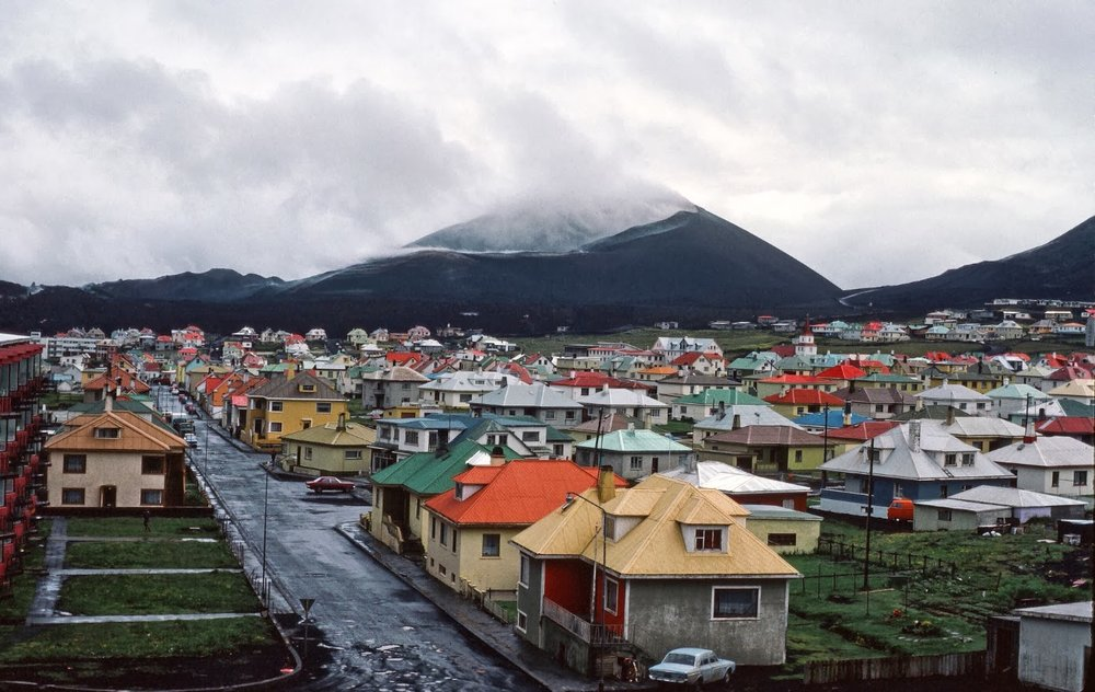The town of Vestmannaeyjar and  Helgafell,  the island's sleeping giant - that's cloud cover and mist, not smoke or fumes coming from the volcano. Photos of the town after the volcano erupted in 1973.