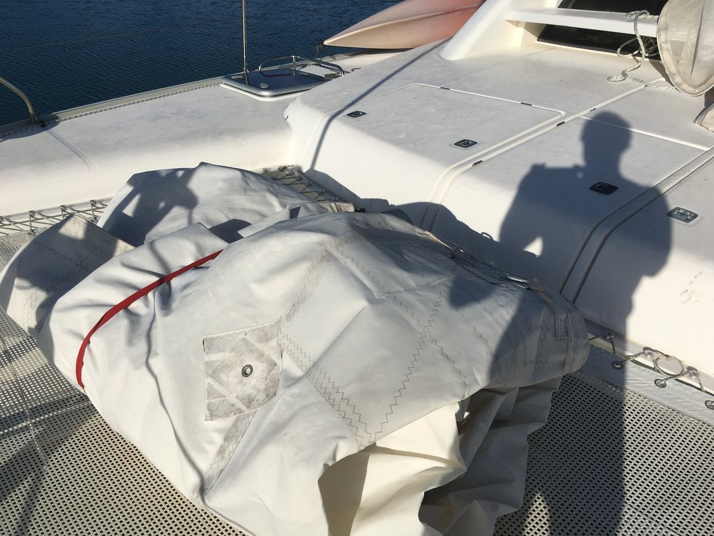 Mystique's mainsail folded and strapped up to store, proved too heavy and bulky for the forward locker storage. So I asked Cristian R. to help me move it to the main salon astern.