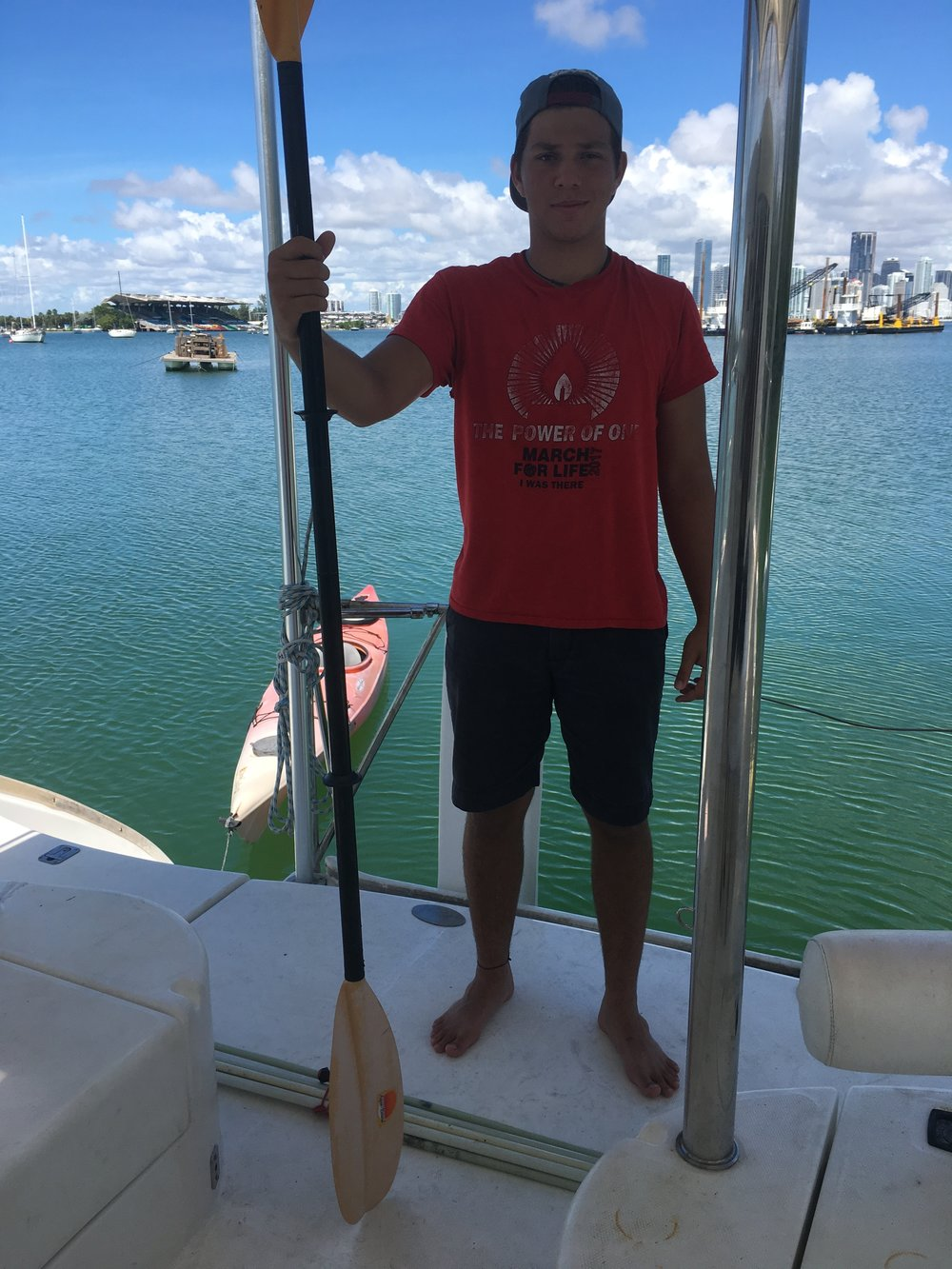 With Miami in the background, Cristian R. poses with his kayak paddle staff.