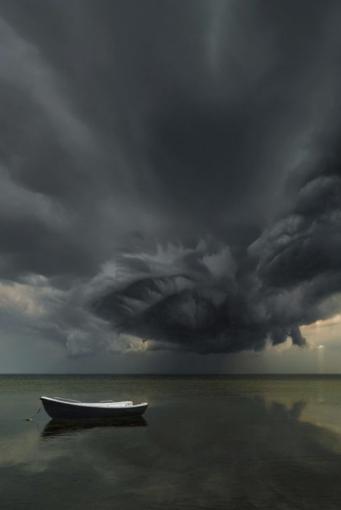A dark and ominous storm drifts over a calm. A contrasting squall floats, shadows and threatens a moored rowboat.