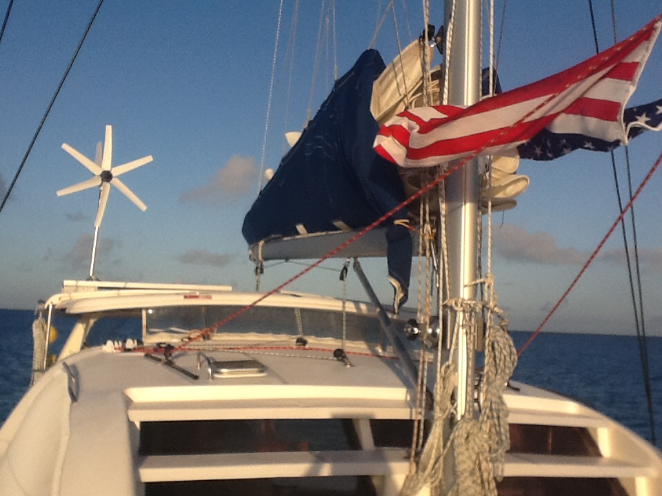 The US flag, the sail cover and the wind generator feel Flow on deck Mystique near Great Sandy Cay in the Turks.