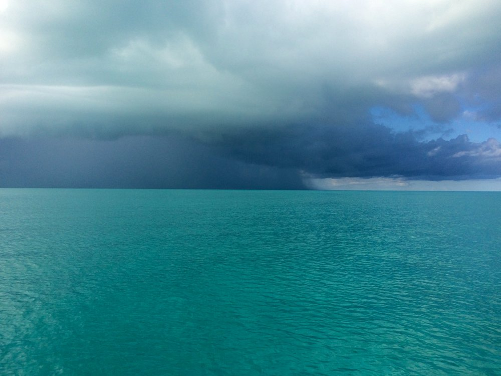A squall approaches as Mystique and I approach it in the southern Exumas in 2016. It's lightning and thunder gave it a nasty appearance, but Mystique and I motored into it just the same. As the sound, fury and torrential downpour encircled and unloaded on me and my vessel, the two of us passed through the storm which dissipated within 10-15 minutes. Part of FLOW is facing it bow first.