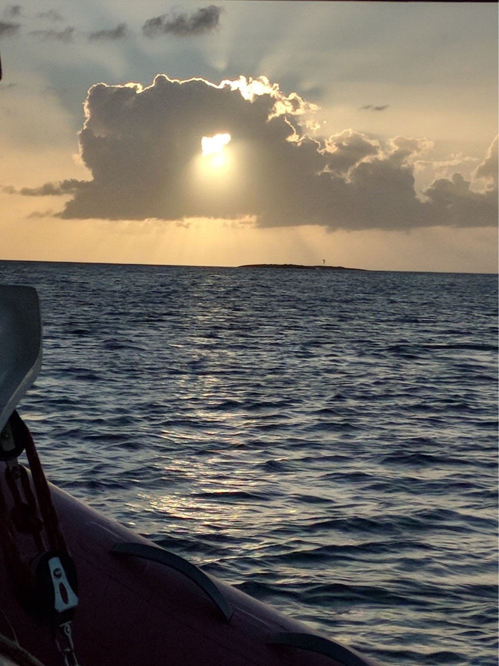 Cloud and sun-setting over Gould Cay near West End, New Providence.