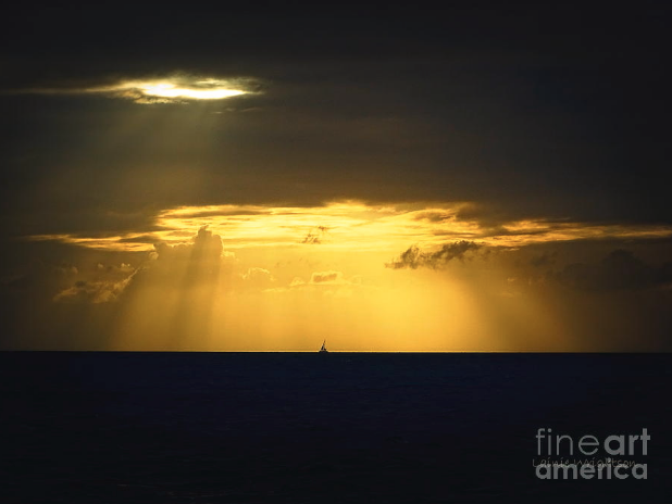Lainie Wrightson's  photo  of a single sail in the Bahamas sailing below and above vast light and dark sky and sea. The clouds appear to wink and smile at Lainie as she captures this sunset shot.
