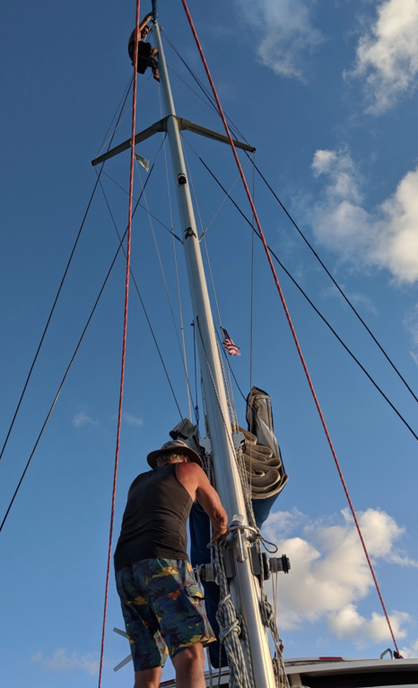Maikel offers to go up our mast to fix the halyard.