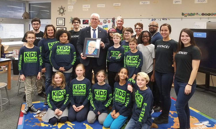 Mayor Collier, holding portrait, is surrounded by Kids for Climate, school officials and IUPUI students.