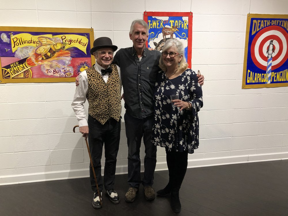 Joe (left) and Bess surround ECI Executive Director Jim Poyser at an exhibit at the Harrison Center for the Arts in January, 2019.