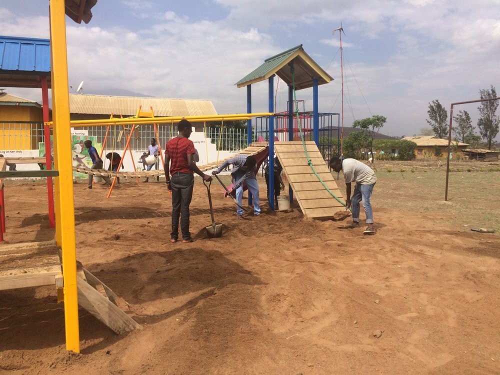 Laying sand on the new playground, which includes top-quality climbing systems made by IBES in Usa River and donated by the Unite For Africa Student Club in Darien, CT.
