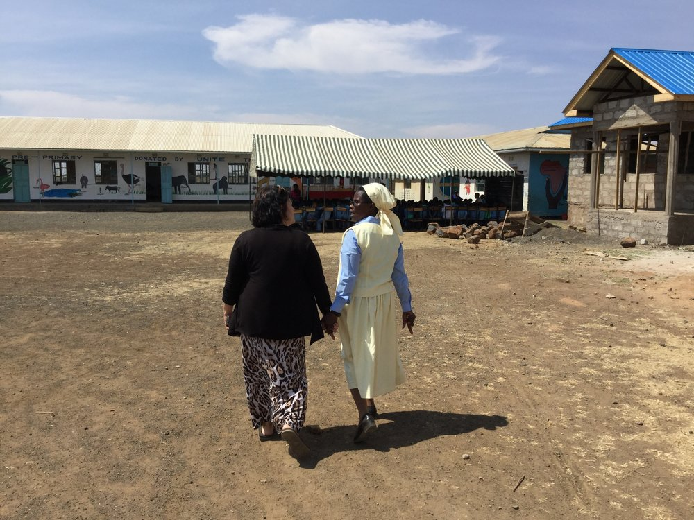 Unite's program manager Deb Marshall and Sister Crispina Mnate, founder & director of St. Joseph's and Heaven stroll in front of the admin block while is was still under construction.