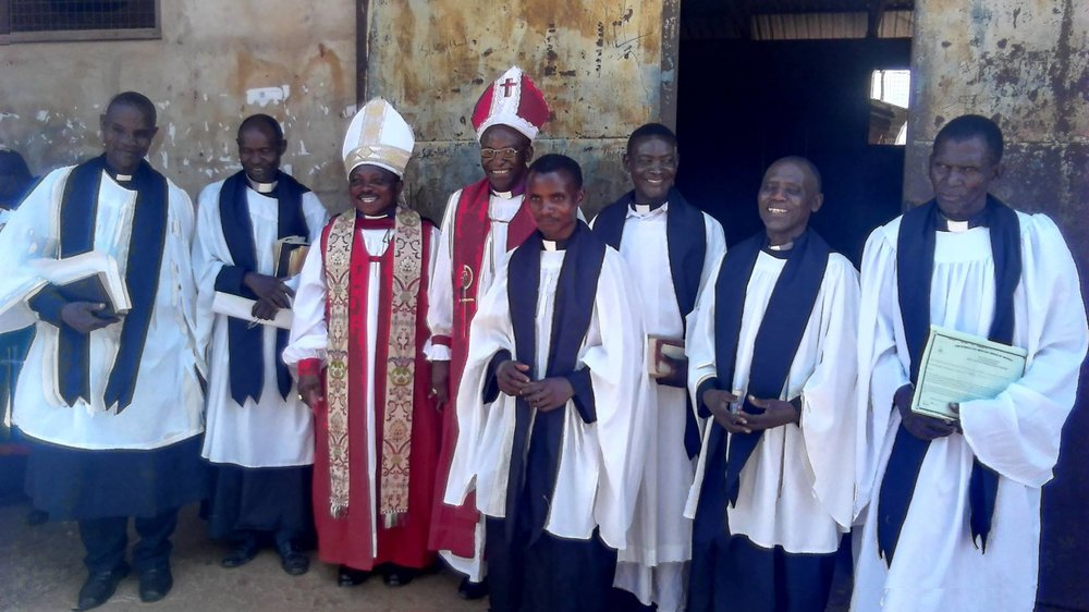 Bishop Chingwaba (center left in red) with fellow clergy members in Tanzania.