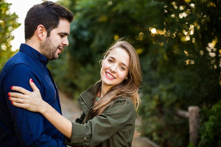 lifestyle smiling engagement portraits, bokeh trees with sun shining through in brooklyn bridge park - www.cassiecastellaw.com