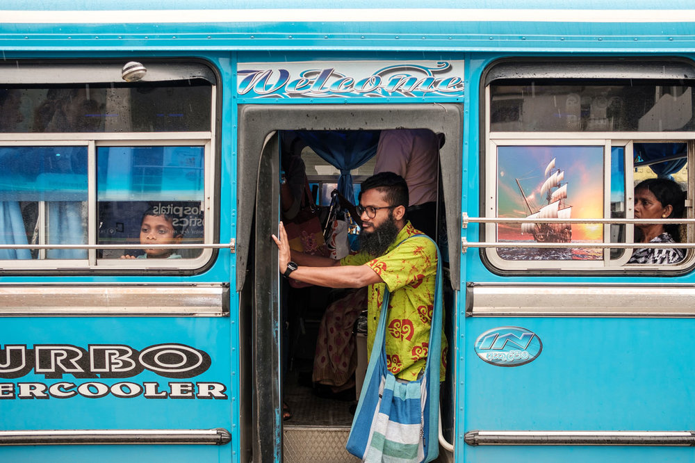 Copy of man in yellow shirt standing in bus door kandy sri lanka