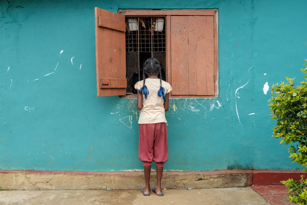 Copy of girl standing in front of a window and turquoise wall in haputale sri lanka