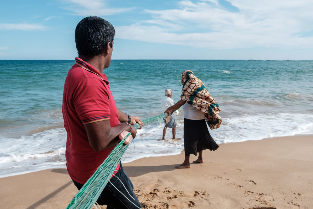 Copy of family on beach pulling fishing net out of ocean in tangalle sri lanka