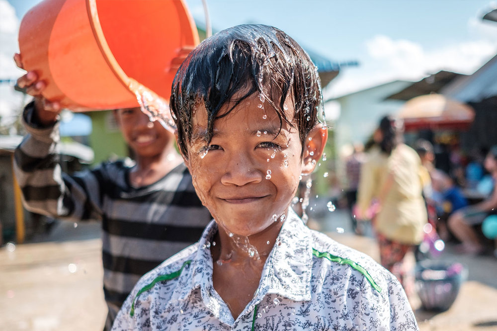 Copy of portrait cambodian boy laughs as his friend douses him with a bucket of water kulturhybrid