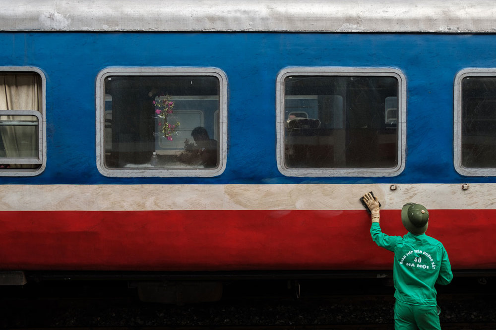 vietnamese man cleaning train in hanoi