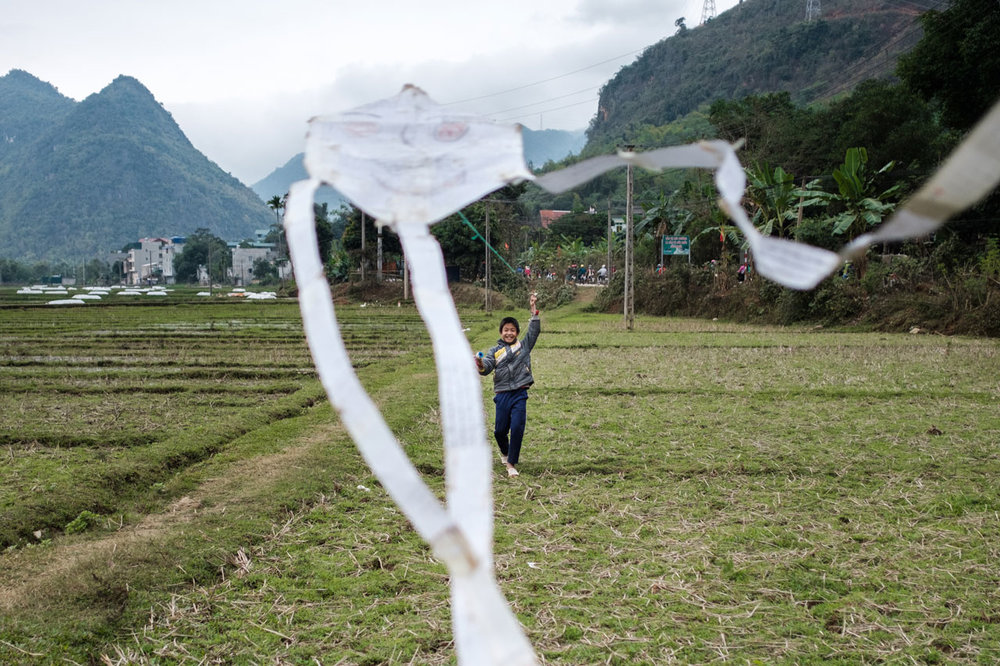 vietnamese boy flying a kite on countryside