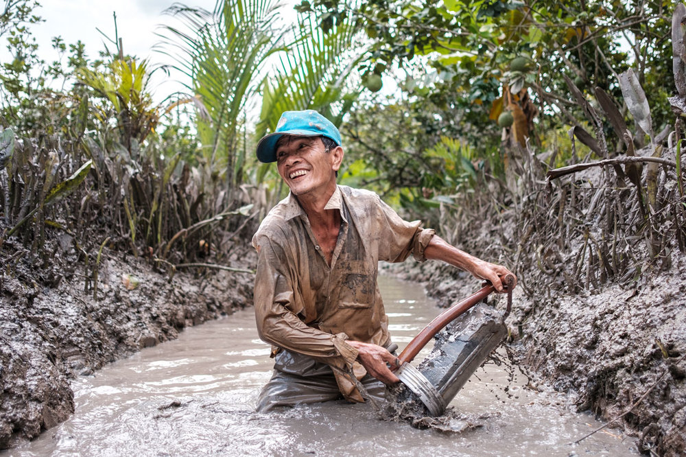vietnamese man from mekong delta collects mud to use it as fertiliser