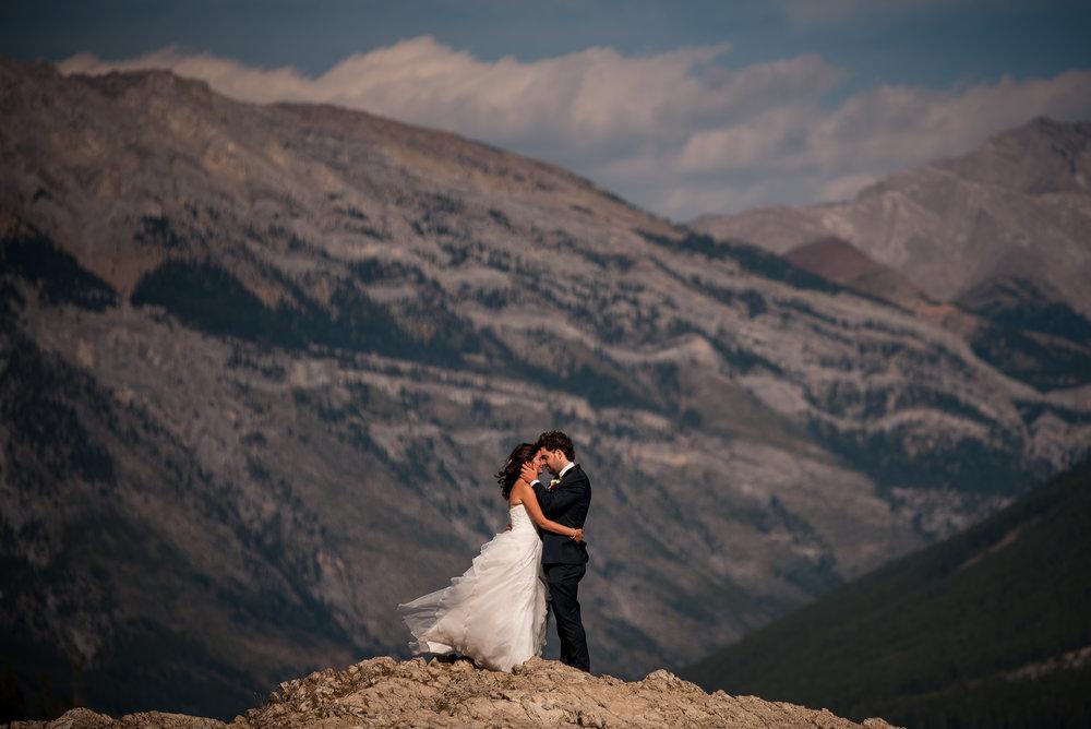 lake minnewanka wedding photos banff wedding couple pose rocks epic landscape portrait kiss calgary banff wedding photographer