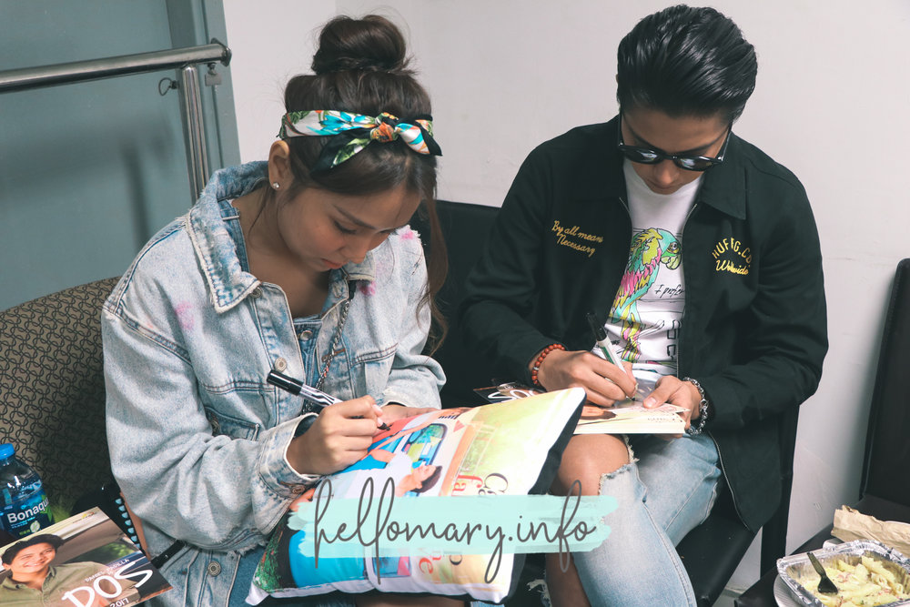 Kath & DJ signing merchandise for the volunteers.