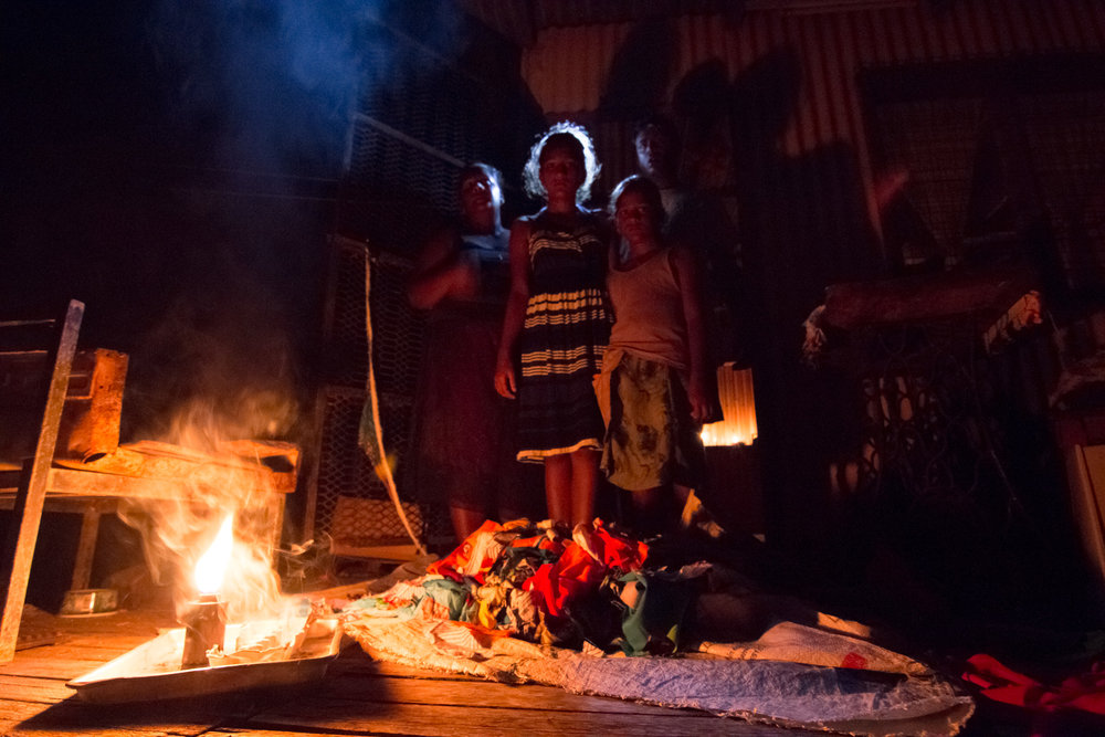 A family in Nausori spend the evening together without electricity due to nationwide power shortages caused after Cyclone Winston swept through the area and made landfall in Fiji on February 20, 2016.