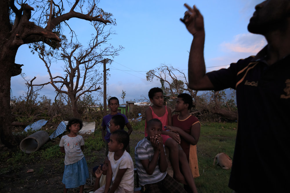 A resident points to his damaged home as children stand behind him in Drau-ni-ivi Village in Rakiraki, currently acting as one of the largest evacuation centers in the country after Cyclone Winston swept through the area and made landfall in Fiji on February 20, 2016.