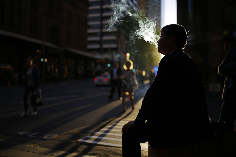 A man smokes a cigarette outside of an office building in central Sydney, Australia. October 25, 2016.