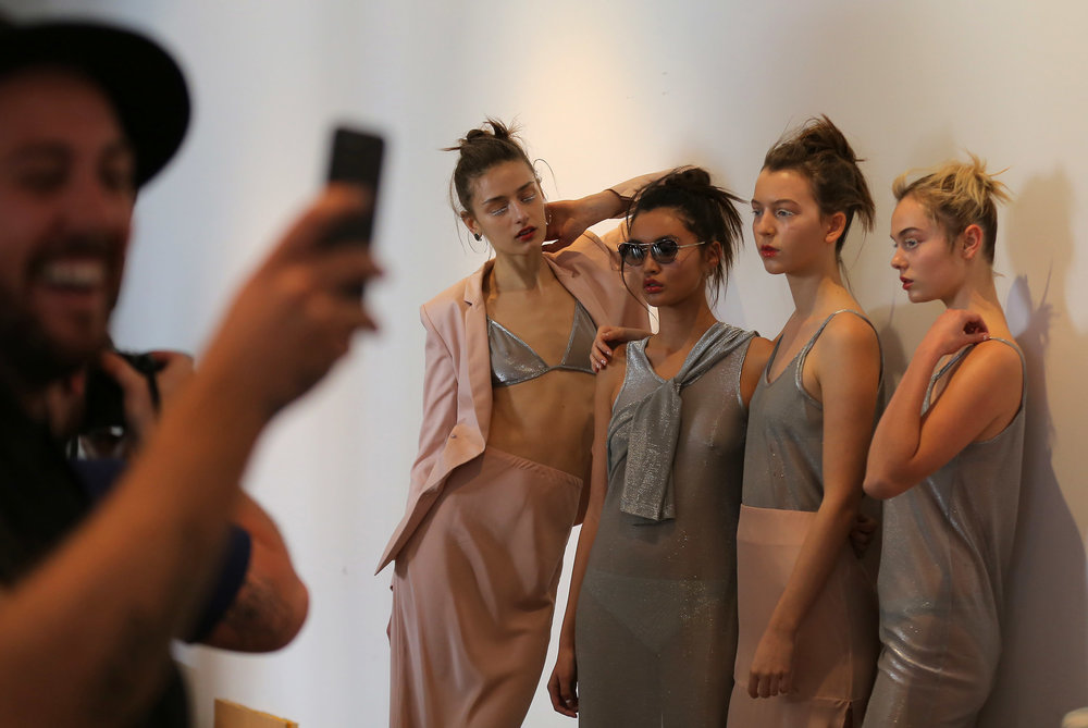Models for designer Gary Bigeni pose backstage during Fashion Week Australia in Sydney, Australia.