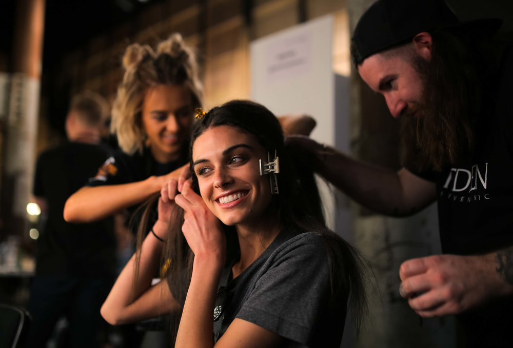A model has her hair prepared back stage before a runway show at Fashion Week Australia in Sydney, Australia.