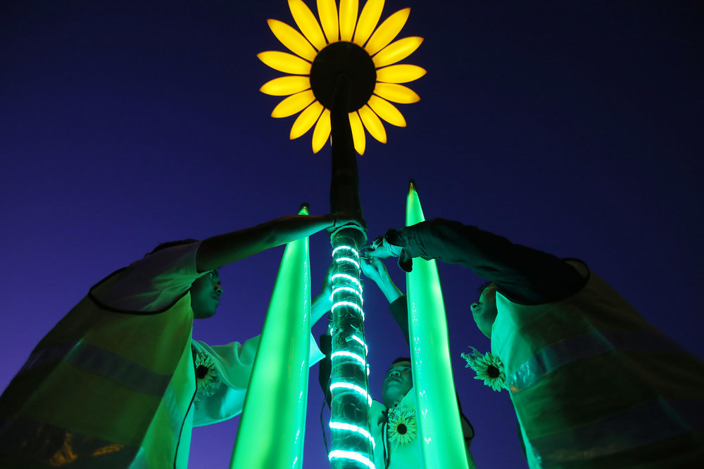 Last minute repairs are made to a giant animated sunflower by artists Francesco Cappuccio & Dutchanee Ongarjsiri before a preview of The Royal Botanic Garden's The Sunflowers installation as part of Vivid Sydney festival of light and sound in Sydney, Australia May 24, 2017.