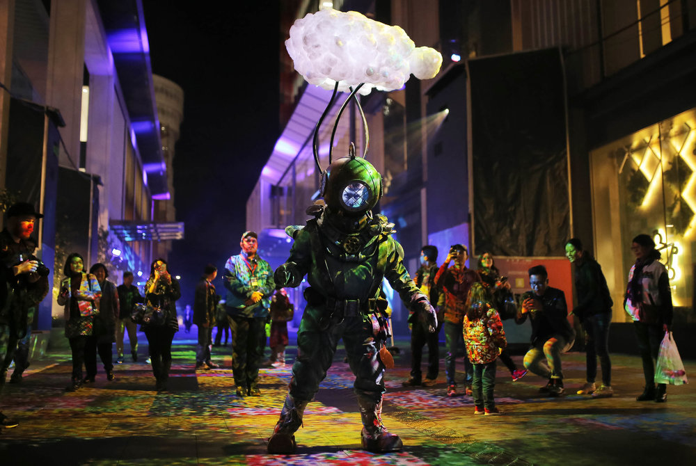 A man wearing an illuminated atmospheric diving suit interacts with revellers as part of the 'What Lies Beneath' installation during the Vivid Sydney festival of light and sound at Barangaroo in Sydney, Australia May 26, 2017.