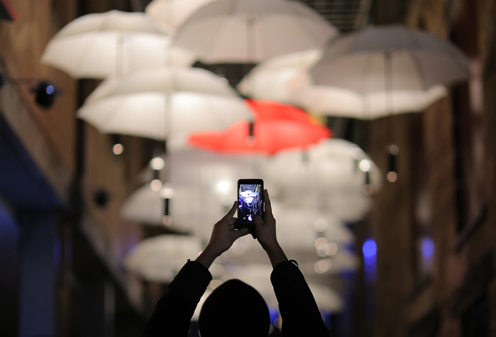 A member of the public takes a photograph of a canopy of umbrellas that are part of an installation titled 'Under My Umbrella' during the Vivid Sydney festival of light and sound in Sydney, Australia, May 27, 2017.