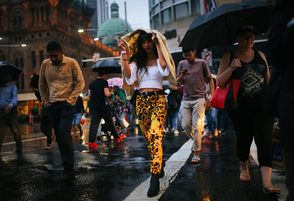 A woman shields her hair from the rain with a jacket as she crosses the street with other pedestrians during a rain shower in central Sydney, Australia.