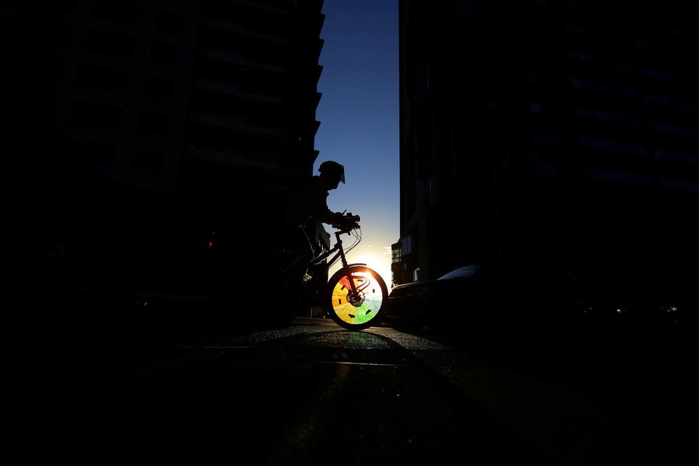 A cyclist rides into a shaft of light between two buildings in Sydney's business district, Australia.