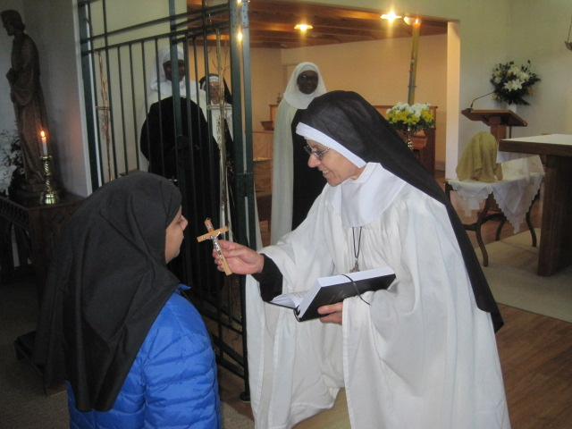 "Rev.Mother Rachel (Prioress) gives a crucifix to Sr Theodora and says ""Hearken O daughter, to the call of Christ as you take up your cross to follow him for he says - 'If anyone will come after me, let him deny himself, take up his cross daily , and follow me.'"""
