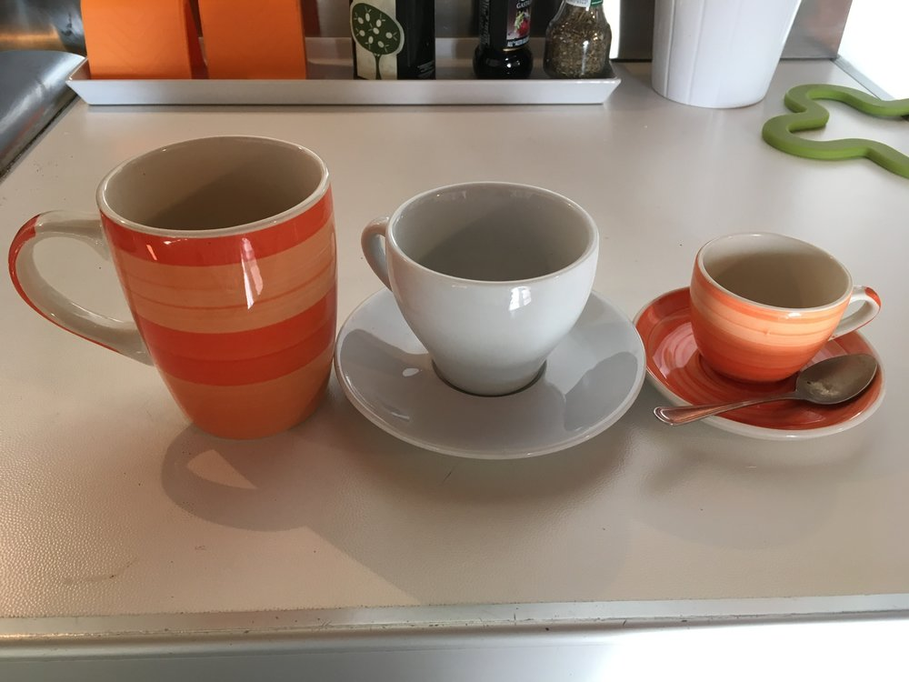 An assortment of cups found in the kitchen - caffe americano, cappuccino, or espresso.