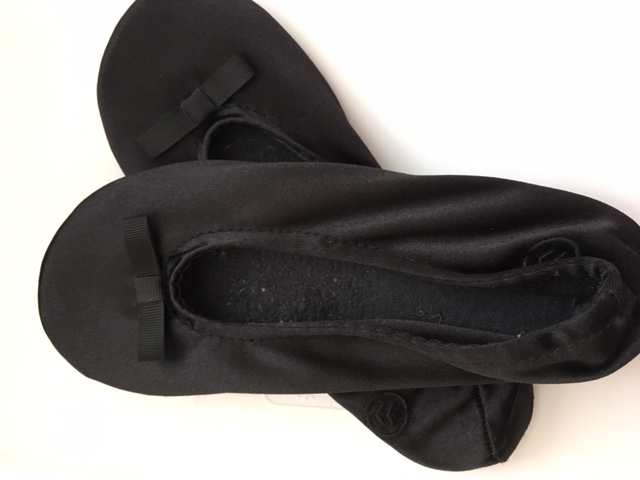 Isotoner brand ballet flat slippers slide into a carry on, have a good sole, and are machine washable.