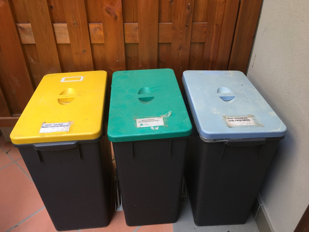 Separate bins, one each for paper, mixed materials, and non-recyclables on the patio of my apartment.  The fourth bin, for organics or compostables, was in my kitchen.