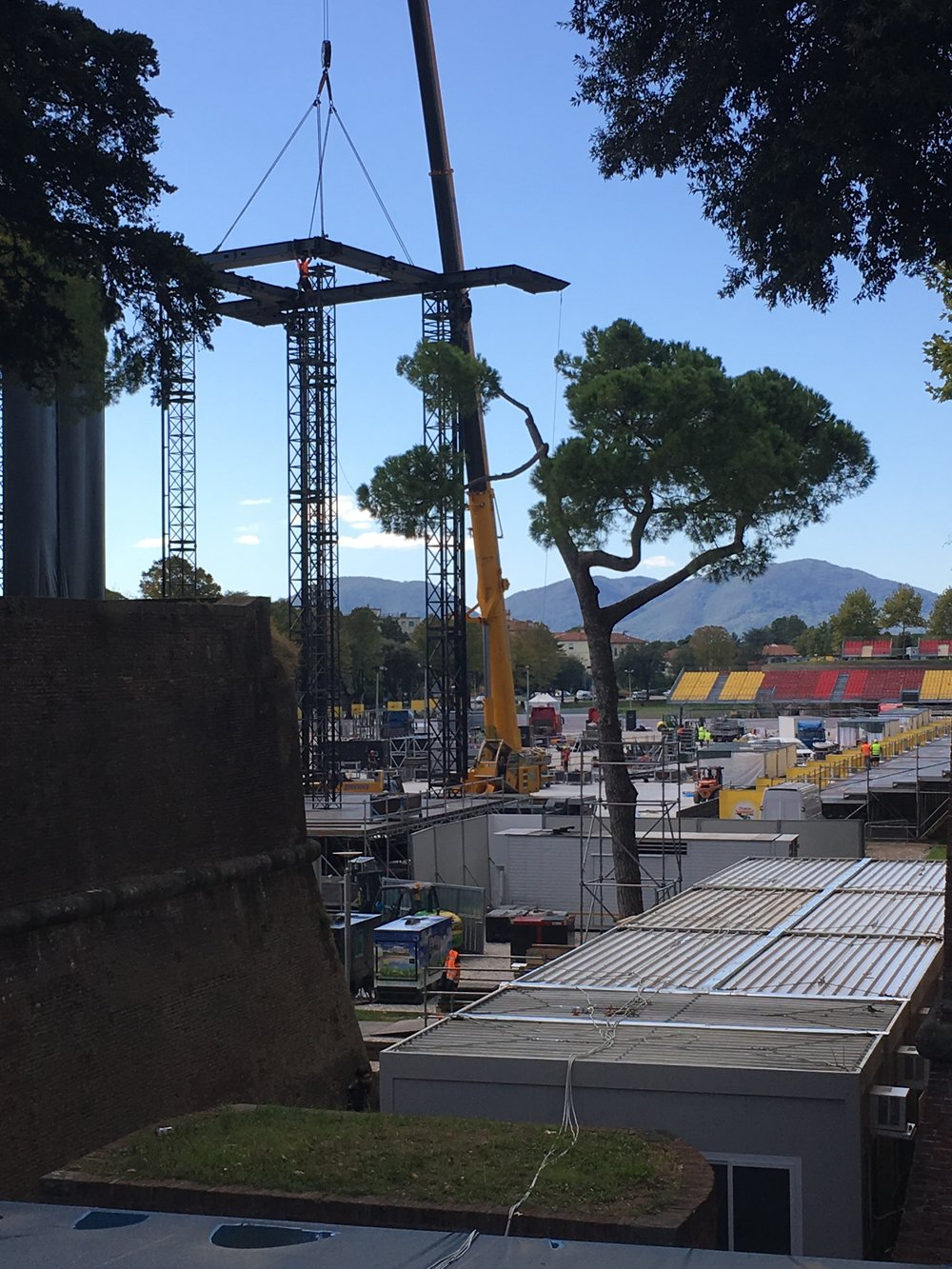 Construction of the stage and seating areas.  Most concert-goers will stand on the grassy field beyond the city walls.
